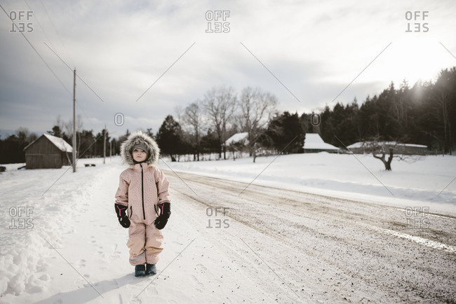 Girl in snowsuit on snowy country road