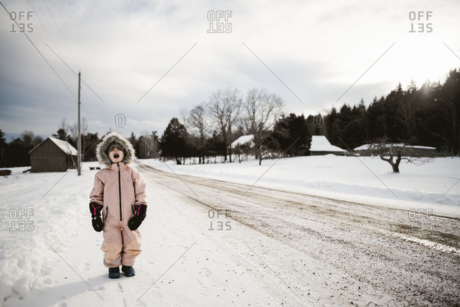 Girl in snowsuit yelling on country road