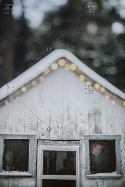 Boy looking out rural shack window