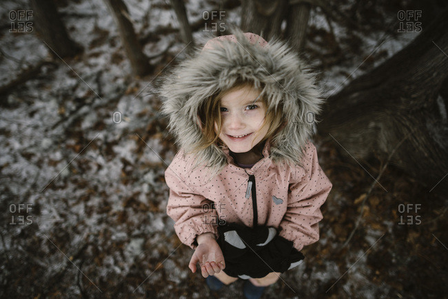 Girl in fur lined hooded coat in forest