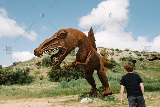 California - March 27, 2017: Boy looking at dinosaur sculpture