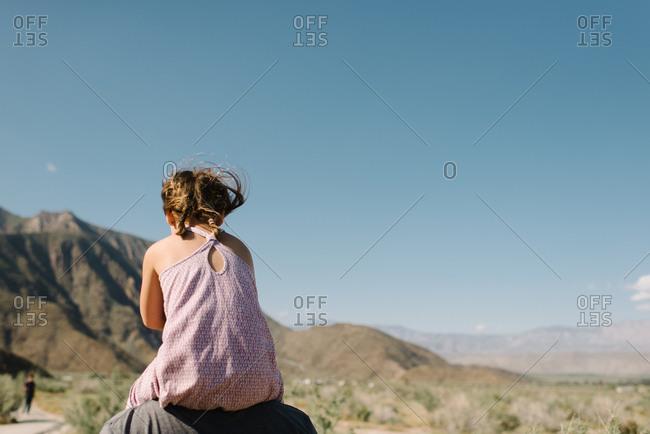 Girl on dad's shoulders in desert