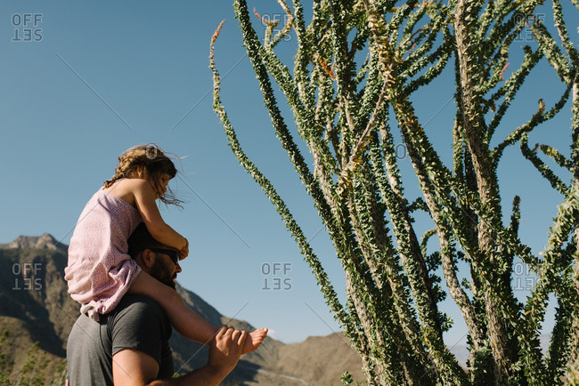 Girl riding dad's shoulders in desert
