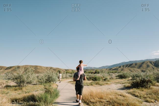Girl riding man's shoulders in desert