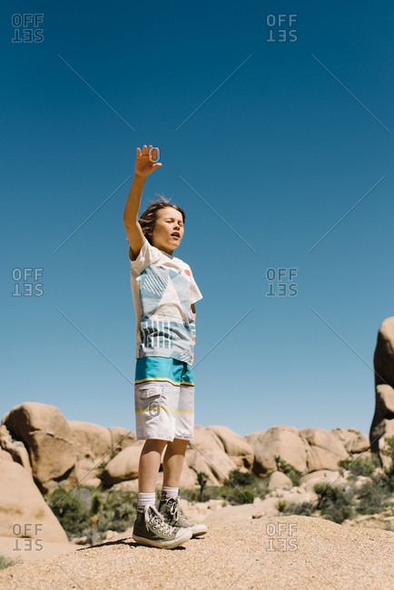 Boy waving on desert rocks