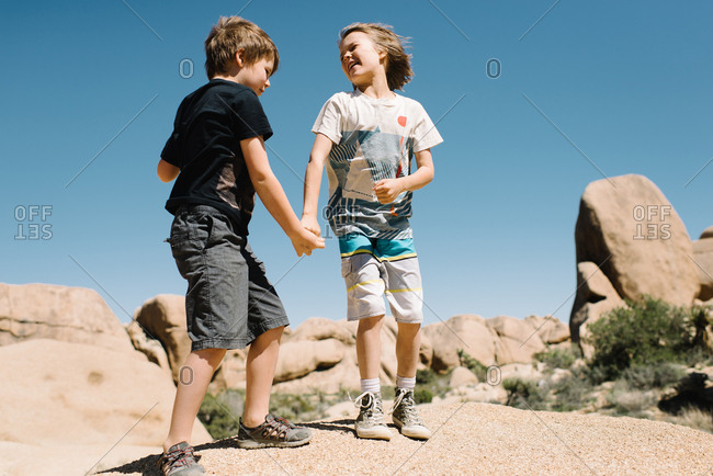 Boys climbing a desert boulder