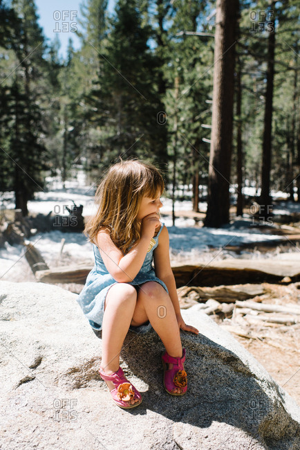 Girl sitting on rock in wilderness