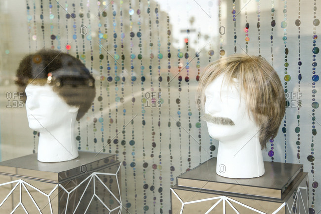 Men's wigs in a storefront window in Los Angeles, California