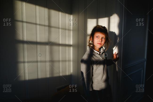 Blonde girl standing in evening window light