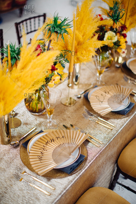 Feathery gold floral arrangements on table with paper fan place markers