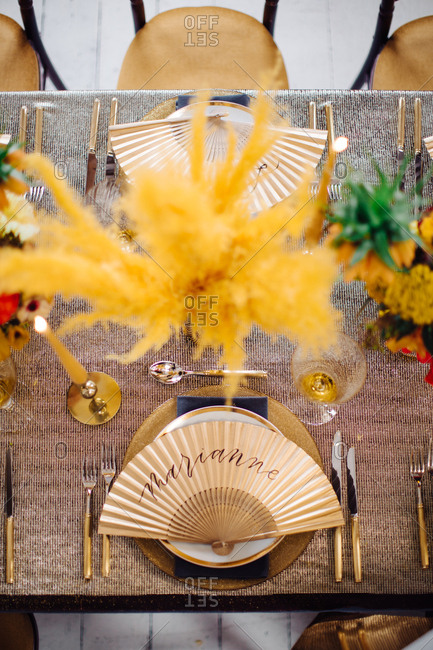 Overhead view of dining table with feathery gold floral arrangements