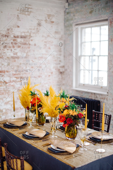 Dining table with feathery floral arrangements and paper fan place markers