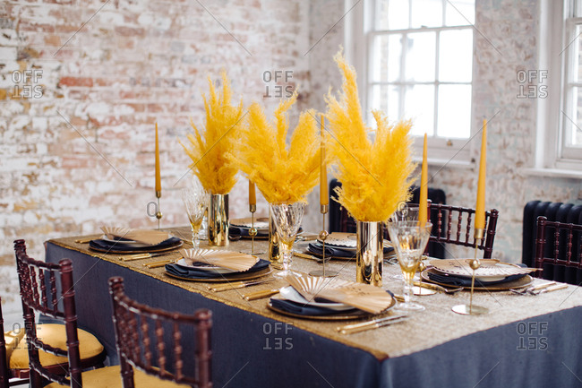 Close-up of dining table set with gold candles and feathery floral arrangements