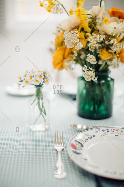 Yellow and white floral arrangements on dining table