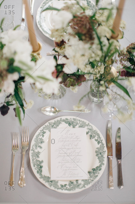 Overhead view of dining table with printed menu card and white wildflowers