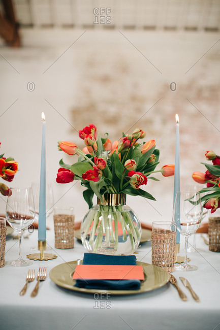 Vase of tulips between candles on dining table