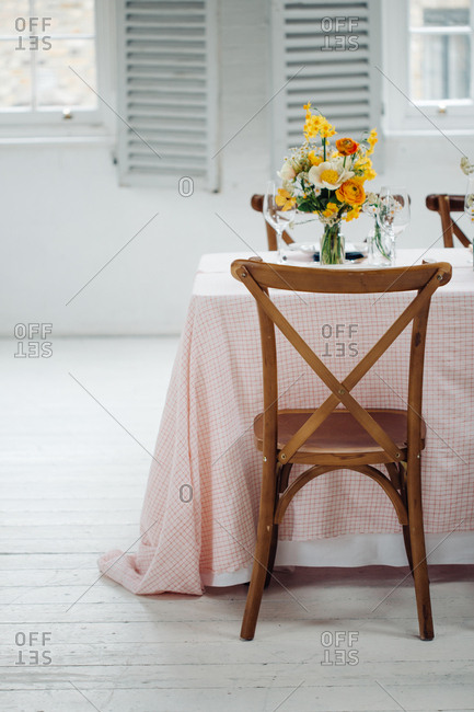 Cross-backed chair at dining table with plaid tablecloth