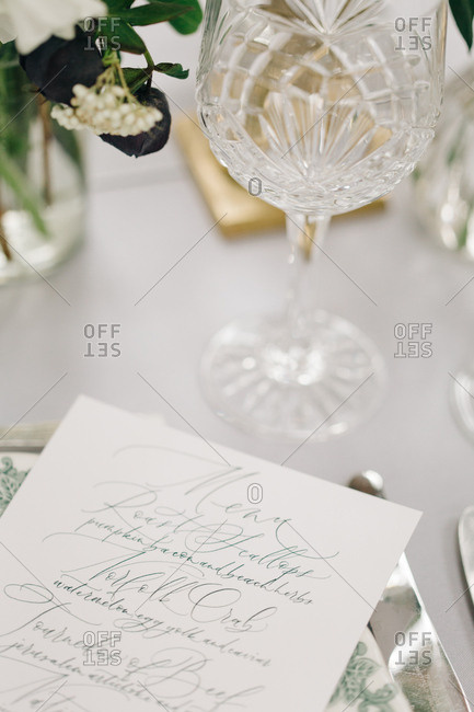Crystal wine glass on dining table with printed menu card