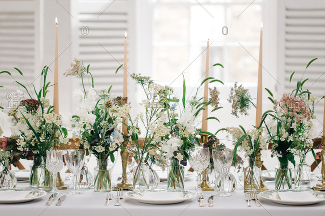 Candles on table with foxtail grass floral arrangements