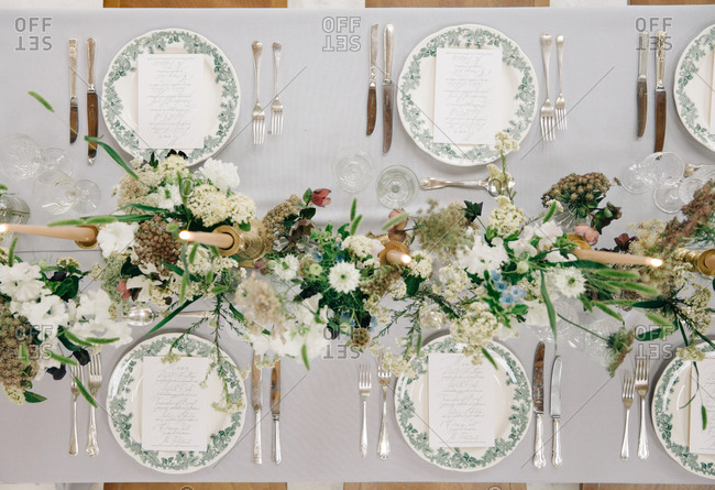 Overhead view of green, white, and beige table decor