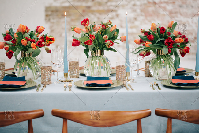 Vases of red and coral tulips on blue dining table