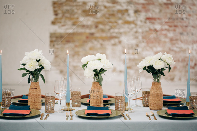 Three wicker-wrapped vases of white peonies on dining table