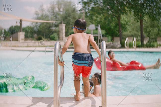 Boy at ladder of swimming pool