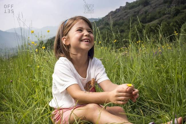 Smiling Young Girl Sitting in Field of Wildflowers