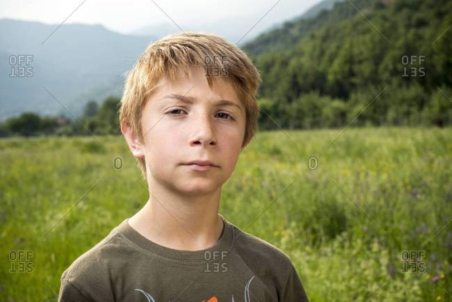 Portrait of Young Boy Standing in Field with Mountains in Background