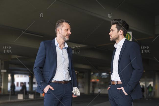 Two businessmen waiting at bus terminal