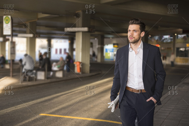 Portrait of young businessman waiting at bus terminal