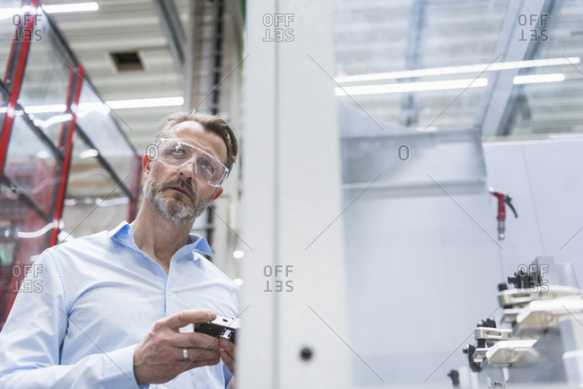 Man wearing safety goggles in factory holding product