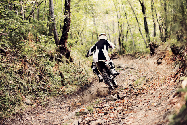 Italy- Motocross biker ridding in Tuscan forest