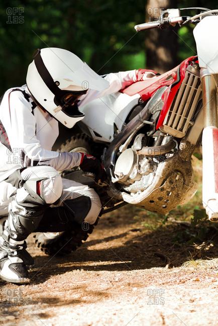 Italy- Motocross biker checking his bike