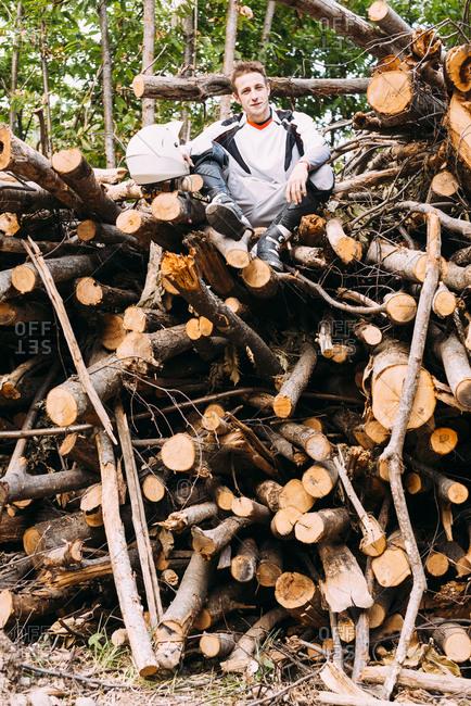 Motocross biker sitting on stack of wood