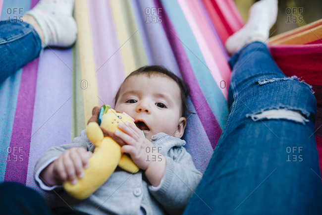 Portrait of baby girl lying on a hammock with her mother
