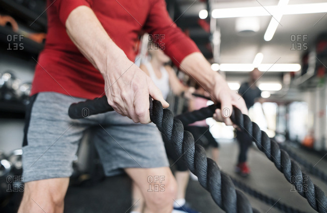 Senior in gym working out with battle ropes