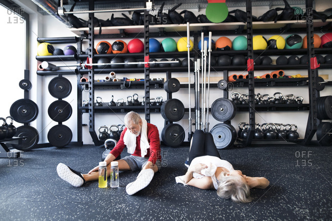 Exhausted senior couple recovering on the floor after working out in gym