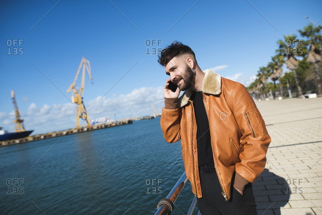 Spain- Cadiz- Young man at the harbor talking on the phone