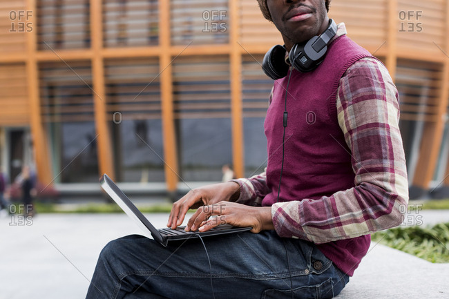 Man with headphones sitting on bench using laptop- partial view