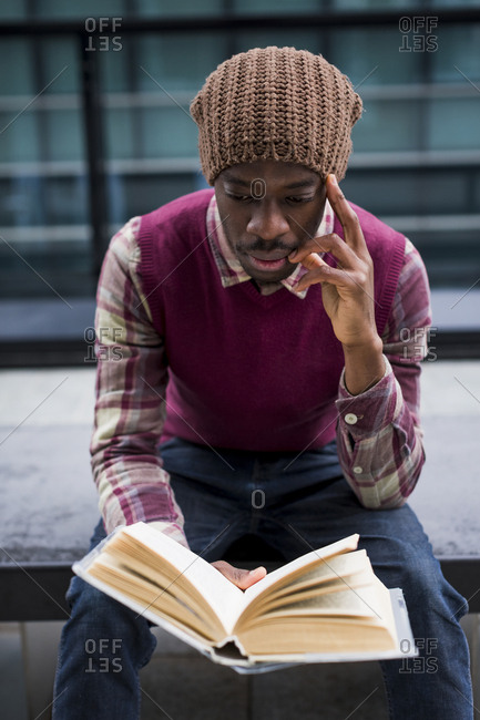 Man sitting on bench reading a book