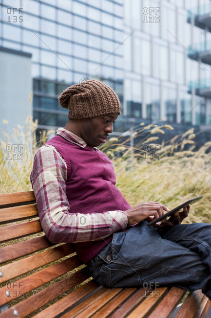 Man sitting on bench using tablet