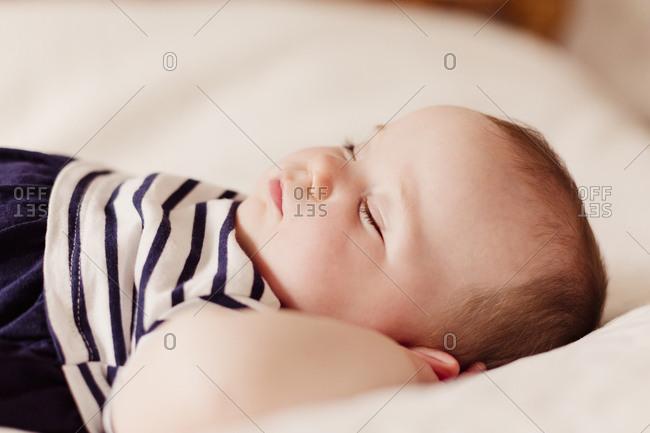 Portrait of baby girl sleeping on bed