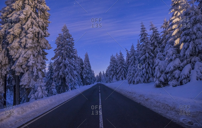 Germany- Lower Saxony- Harz National Park- country road in winter lin the evening