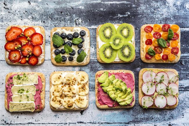 Two rows of various garnished sandwiches