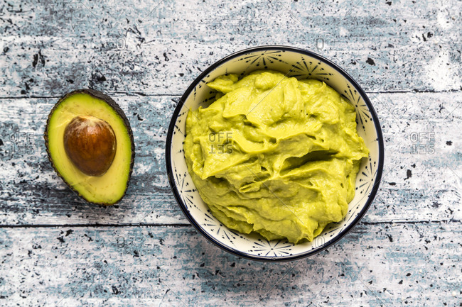 Bowl of avocado hummus and half of avocado