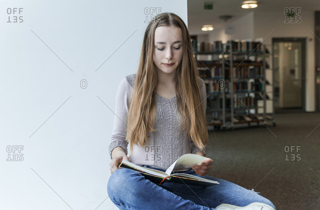 Teenage girl reading book in a public library