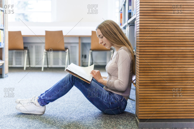 Teenage girl sitting on the floor in a public library reading book
