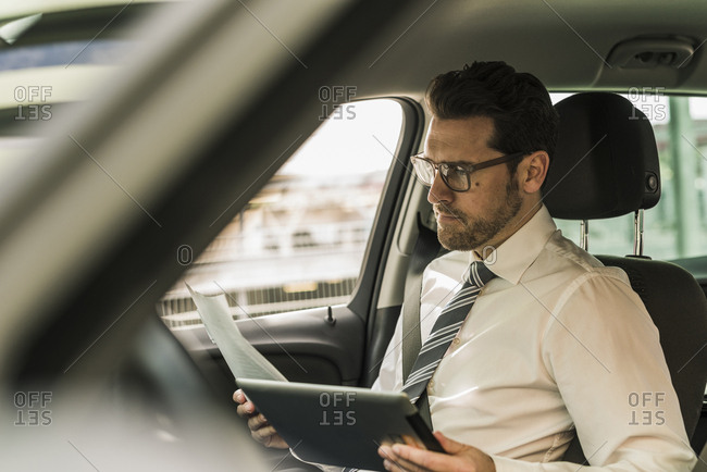 Successful businessman sitting in car using digital tablet