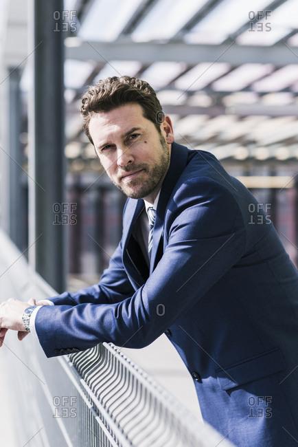 Businessman standing on parking level- portrait